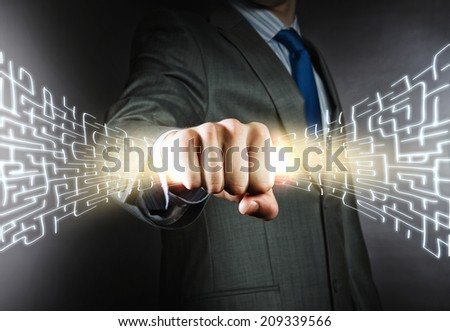 Close up of businessman hand holding labyrinth hologram in fist