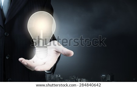 Close up of businessman hand holding light bulb - stock photo