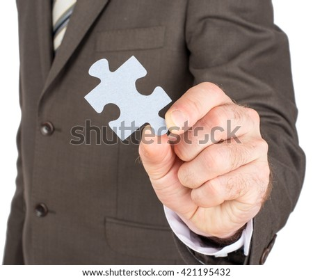 Close up of businessman hand holding puzzle piece isolated on white background