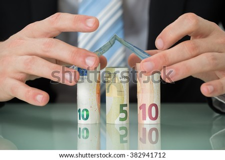 Close-up Of Businessman Hand Making House Of Euro Banknotes