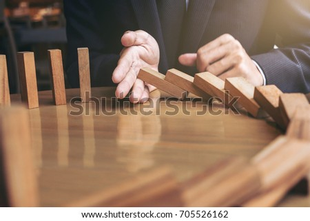 Close up of businessman hand Stopping Falling wooden Dominoes effect from continuous toppled or risk, strategy and successful intervention concept for business.