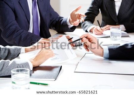 Close-up of businessman hand with pen explaining a financial plan to colleagues at meeting - stock photo