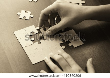 Close-up Of Businessman Hands Completing Jigsaw Puzzle - stock photo