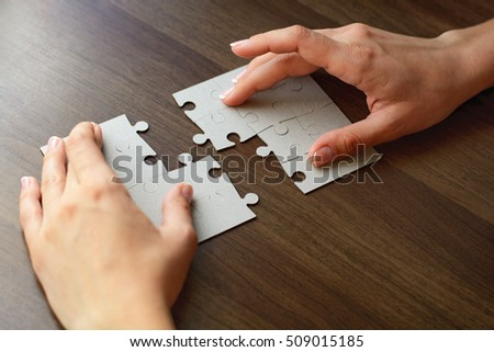 Close Up Of Businessman Hands Completing Jigsaw Puzzle