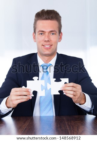 Close-up Of Businessman Hands Connecting Jigsaw Puzzle - stock photo
