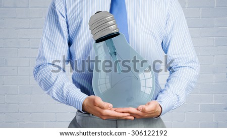 Close up of businessman hands holding glass light bulb - stock photo