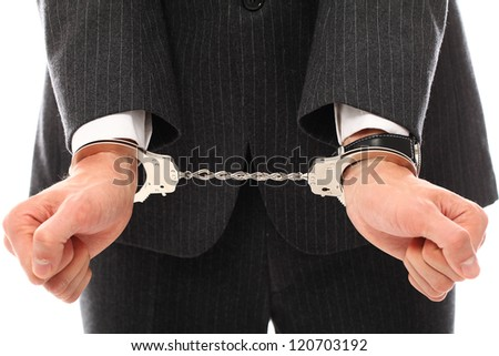 Close up of businessman hands in handcuffs over a white background - stock photo
