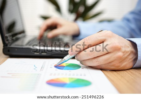 Close up of businessman hands reviewing business report and typing on laptop computer - stock photo