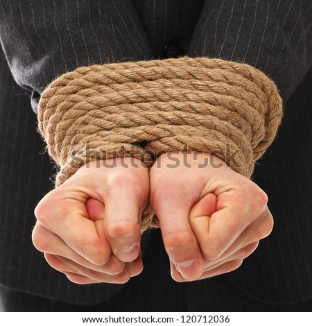 Close up of businessman hands tied with rope together - stock photo