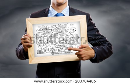 Close up of businessman holding frame with business sketches - stock photo
