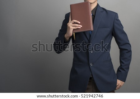 Close up of businessman in blue suit holding books on gray background