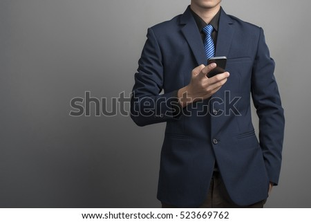 Close up of businessman in blue suit using smartphone on gray background