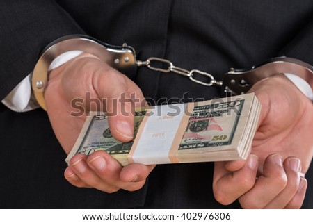 Close-up Of Businessman In Handcuffs Holding Dollars For Bribe - stock photo