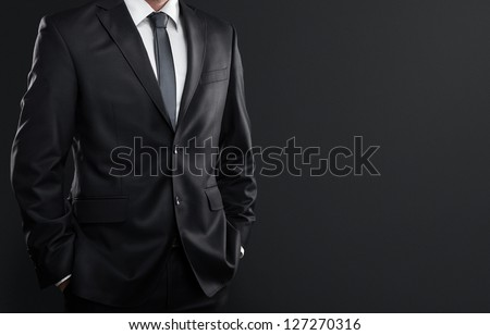 Close up of businessman in suit over dark gray background with copy space