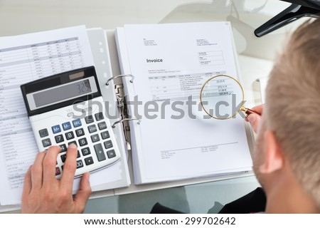 Close-up Of Businessman Inspecting Bills With Magnifying Glass While Using Calculator - stock photo