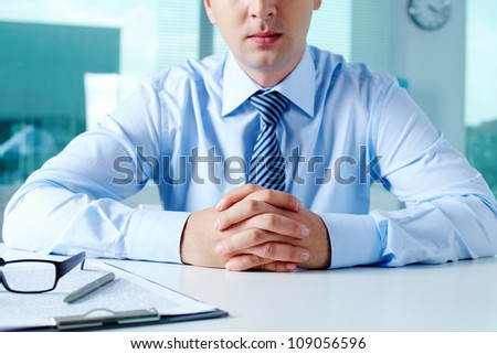 Close-up of businessman keeping fingers crossed in front of himself - stock photo