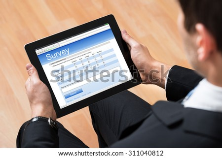 Close-up Of Businessman Looking At Blank Online Survey Form On Digital Tablet - stock photo