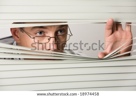 Close-up of businessman peeking out of Venetian blind - stock photo