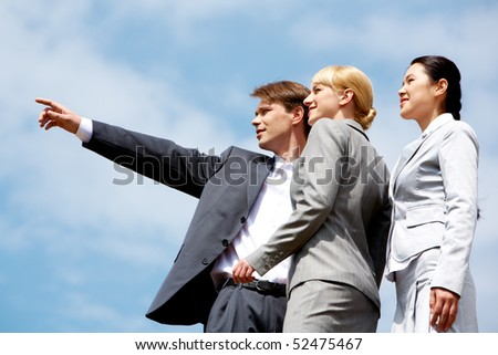 Close-up of businessman pointing at something while two elegant ladies looking at it