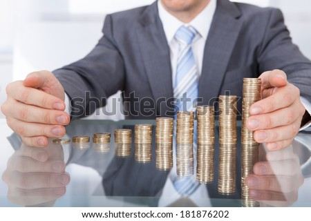 Close-up Of Businessman Protect Stack Of Coins For Business - stock photo