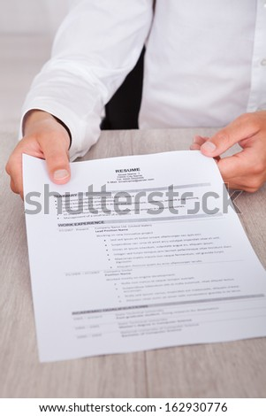 Close-up Of Businessman's Hand Holding Resume On Desk - stock photo