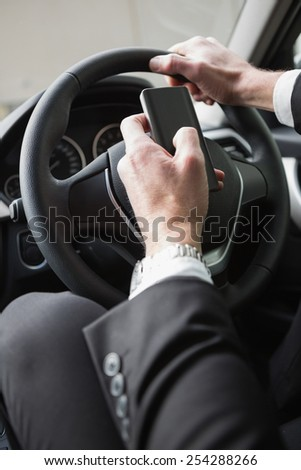 Close up of businessman sending a text message in his car - stock photo