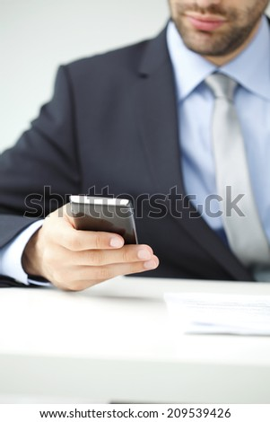Close-up of businessman sitting at desk and using mobile. Small business,  - stock photo