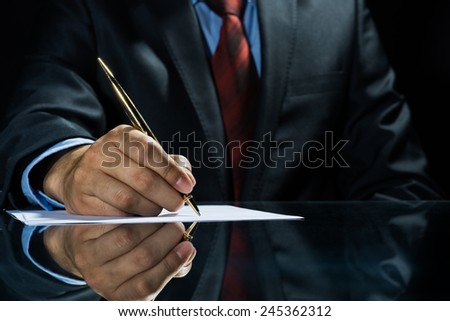 Close up of businessman sitting at table and signing document - stock photo