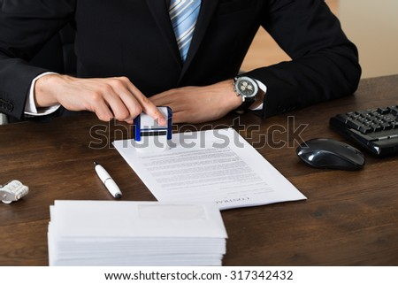 Close-up Of Businessman Stamping Contract Document Paper At Desk - stock photo