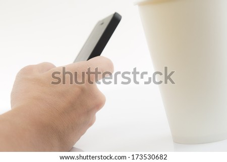 Close-up Of Businessman Using Cell Phone with coffee cup