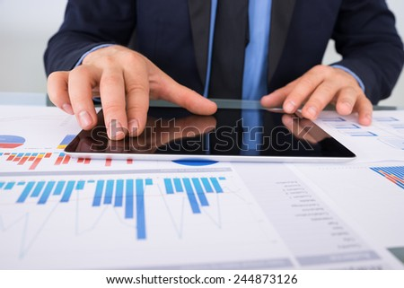Close-up Of Businessman Using Digital Tablet Kept Of Documents - stock photo