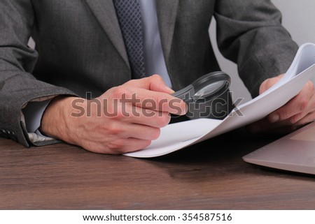 Close up of businessman using loupe for reading contract. Magnifying Glass and document. Lawyer minutely checking documents - stock photo