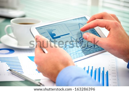Close-up of businessman using tablet computer to work with financial data - stock photo