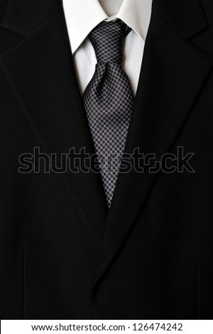 Close up of businessman wearing a tie, shirt, and suit.