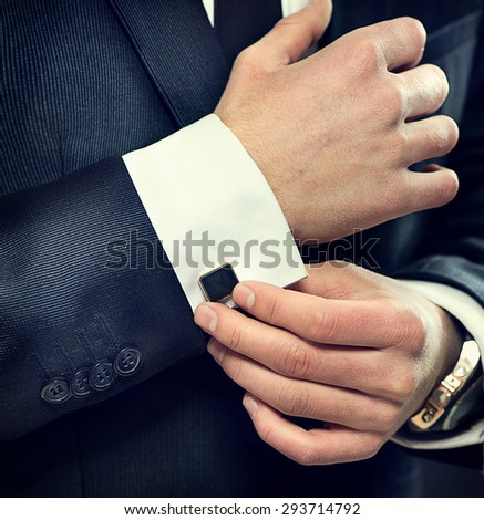 Close up of businessman wearing cufflinks. Elegant young fashion business man wearing suit - stock photo
