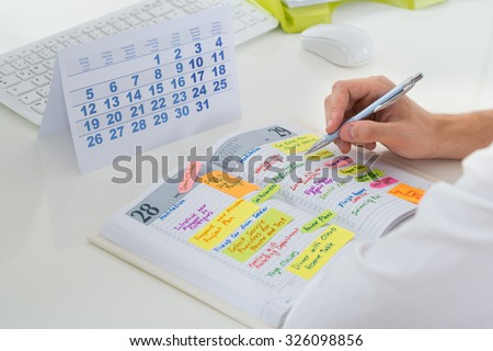 Close-up Of Businessman With Calendar Writing Schedule In Diary - stock photo