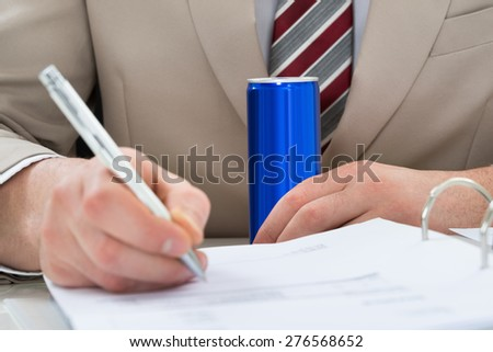 Close-up Of Businessman With Drink Can And Writing On Document - stock photo