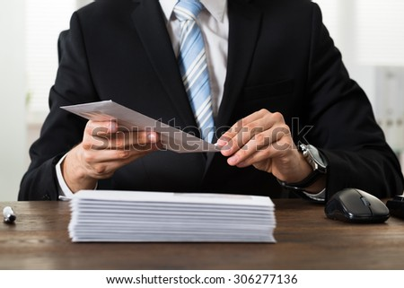 Close-up Of Businessman With Envelopes At Desk In Workplace - stock photo