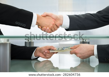 Close-up Of Businessman With Money Handshaking With His Business Partner - stock photo