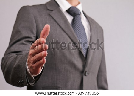 Close up of businessman with open hand ready to seal a deal gesturing a hand shake. Meeting new business partners, partnership, negotiations, presentation - stock photo