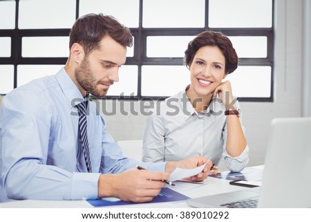 Close-up of businessman working while happy female colleague sitting beside - stock photo