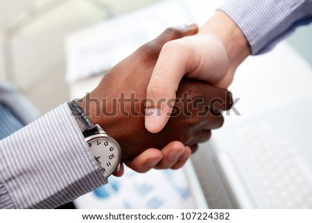 Close-up of businessmen shaking hands, Caucasian and African-American - stock photo