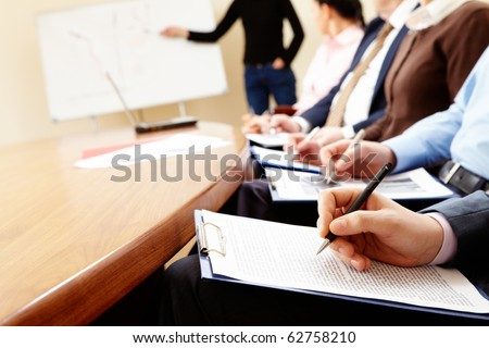 Close-up of businesspeople hands holding pens and papers near table at business seminar - stock photo