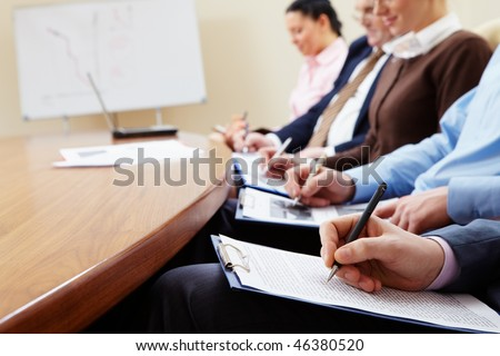 Close-up of businesspeople hands with documents writing at lecture - stock photo