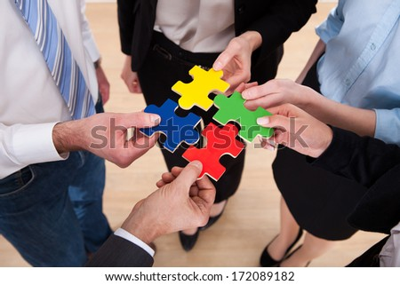 Close-up Of Businesspeople Holding Multi Colored Jigsaw Puzzle