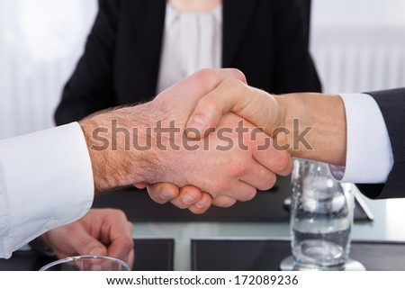 Close-up Of Businesspeople Shaking Hand In Front Of Colleague - stock photo