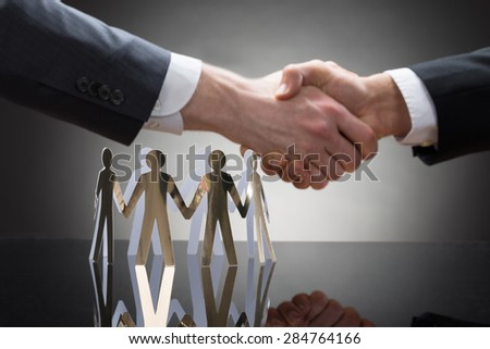 Close-up Of Businesspeople Shaking Hands With Paper Cutout Figures - stock photo