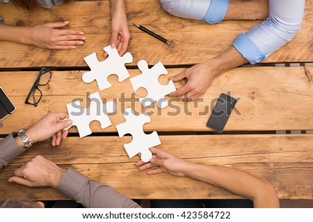 Close-up of businesspeople solving jigsaw puzzle. Closeup of business people wanting to put four pieces of puzzle together. Businesspeople trying to solve problem with the help of jigsaw puzzle. - stock photo