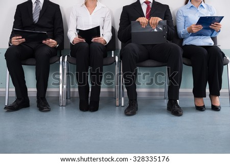 Close-up Of Businesspeople With Files Sitting On Chair - stock photo