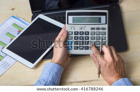 Close-up Of Businessperson Calculating Budget With Calculator At Desk - stock photo